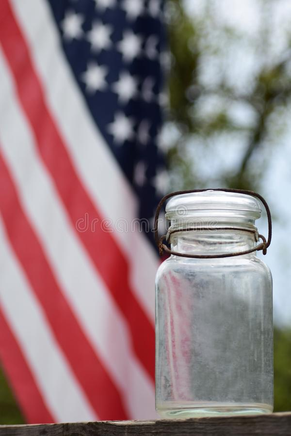 Antique canning jar with the American flag. An antique wire bail canning jar with a waving American flag in the background royalty free stock photo