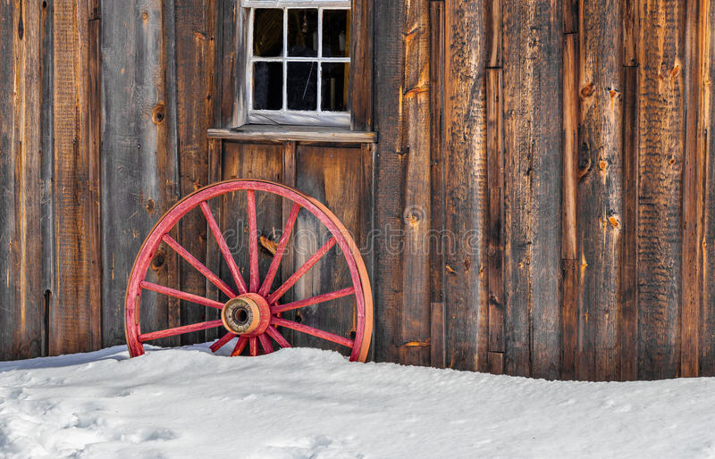 Antique Wood Old Red Wagon Wheel Snow. Wooden cabin with old red wagon wheel under window in winter royalty free stock images