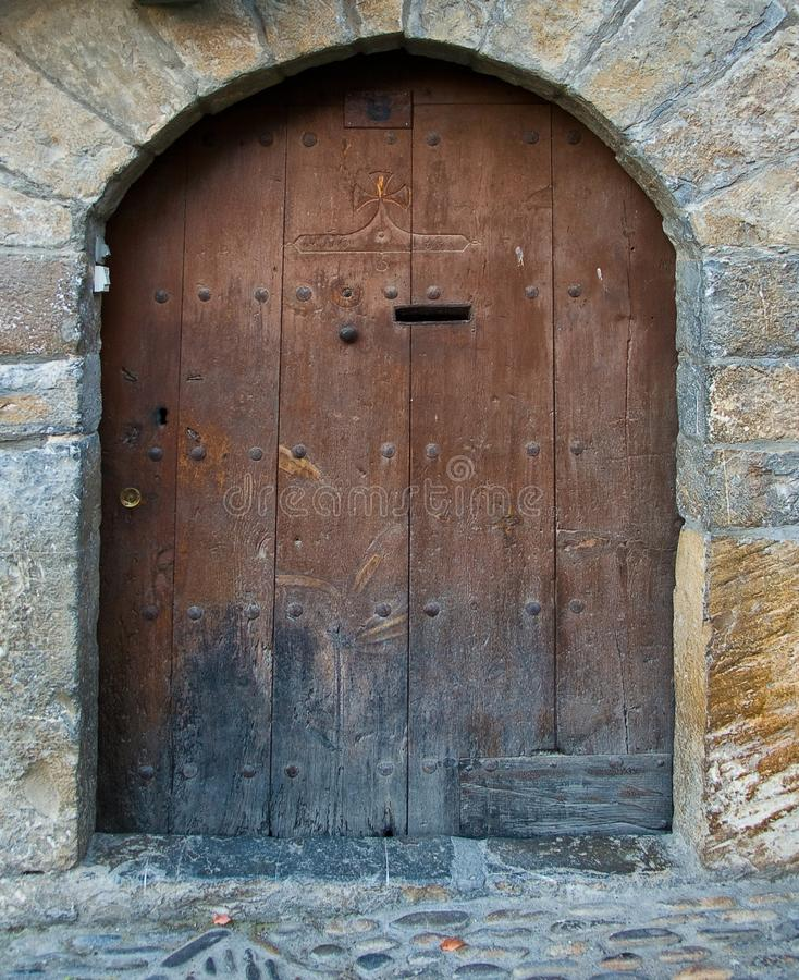 Antique wooden arch door and mailbox. Old door half-point arch of a leaf and wooden mailbox with forge nails in the Pyrenees of Huesca.1 stock image
