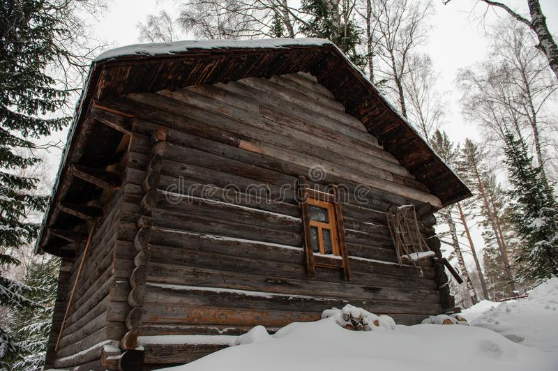 Antique wooden barn house. In winter forest. Retro building of the early 19th century stock images
