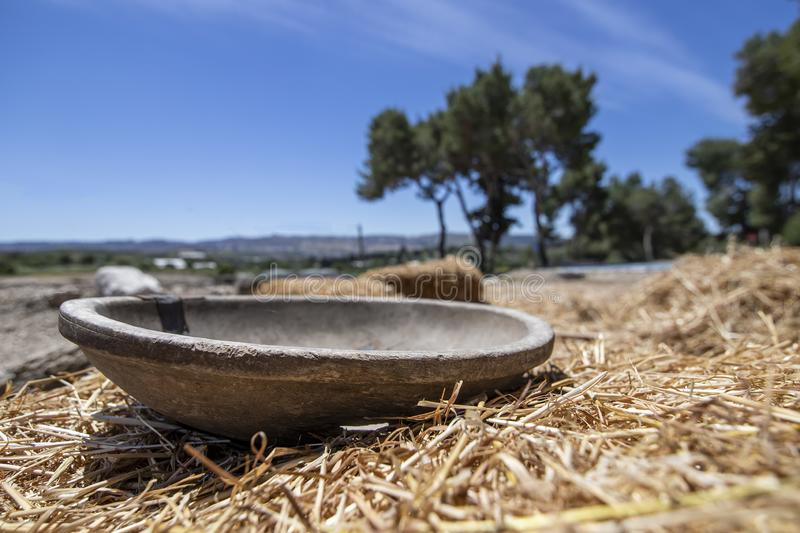 Antique wooden bowl lying on golden straw in the ancient city of Zipori. Israel. stock photography