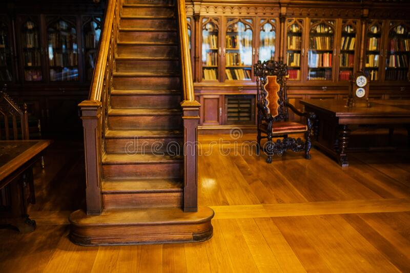Antique wooden cabinet. Library with bookshelves and desk. Classic interior. Books on the shelves. Wooden stairs. Vintage office. stock photography
