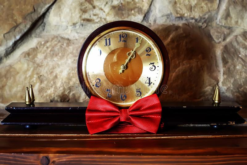 Antique wooden clock and red butterfly for the groom on a stone background, morning of the groom, wedding accessories stock image