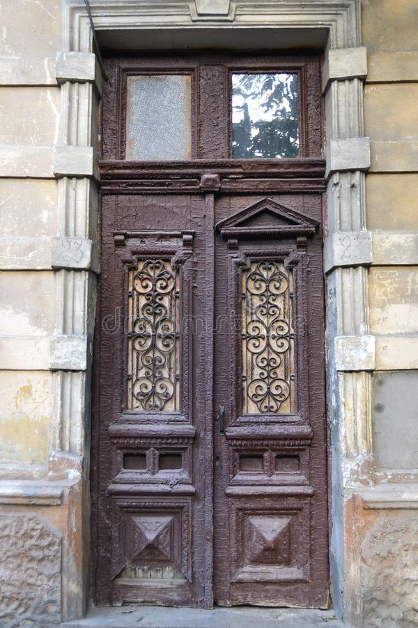 Antique wooden door with forged window frames royalty free stock photo
