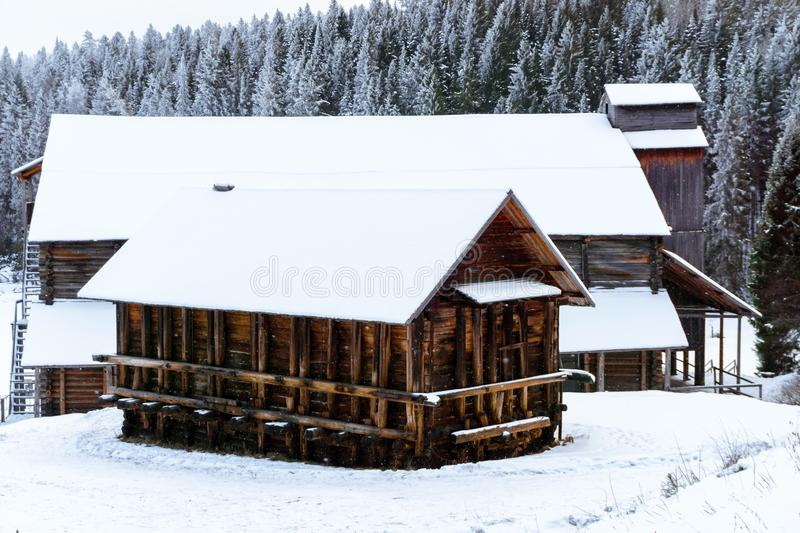 Antique wooden industrial architecture. Complex of traditional wooden warehouses of a salt-mining plant of the 19th century in a winter landscape on the bank of stock image