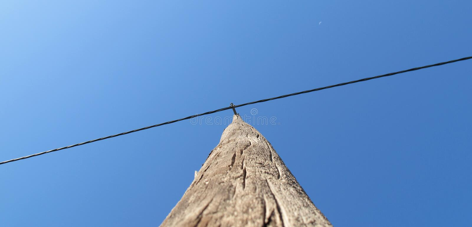 Antique wooden pole to telephone. A antique wooden pole to telephone wires on the clear sky stock images