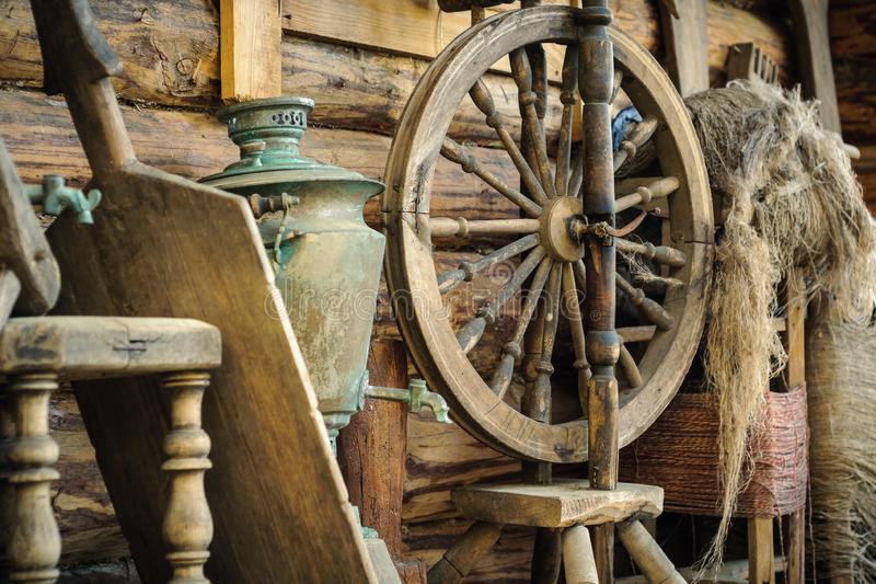 Antique wooden spinning wheel with accessories and old household items against a rough wooden log wall. Antique broken wooden spinning wheel with accessories and stock photos