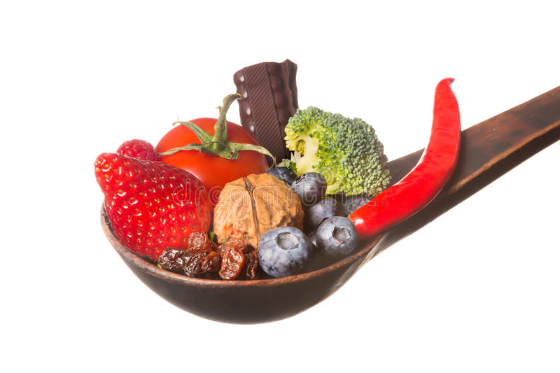 Spoonful of antioxidants. Antique wooden spoon filled with antioxidants fruits and vegetables stock photography