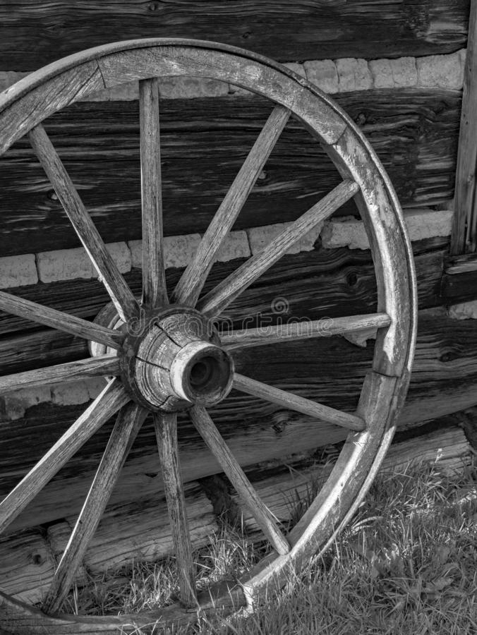 Antique wooden wagon wheel against wooden barn. stock photos