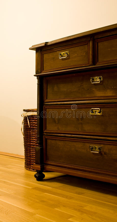 Antiquity. Antique wooden dresser with laundry bin on parquet floor royalty free stock photo