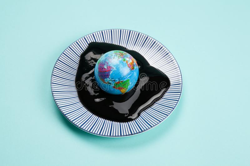 The planet earth drowned in an oil spill. An antistress ball representing the planet earth drowned in an oil spill. Minimal still life color photography stock photography