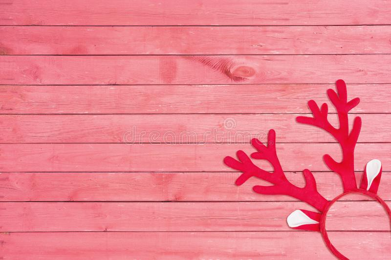Antlers of a deer headband on pink wooden background. Toy reindeer horns on pink wooden texture stock photos