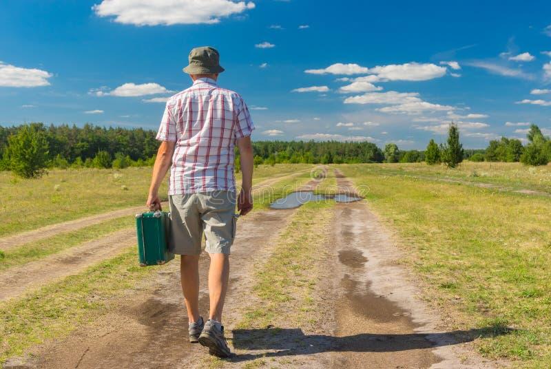 Antolhos vestindo, camisa e chapéu do homem maduro andando em uma estrada secundária do verão imagens de stock royalty free