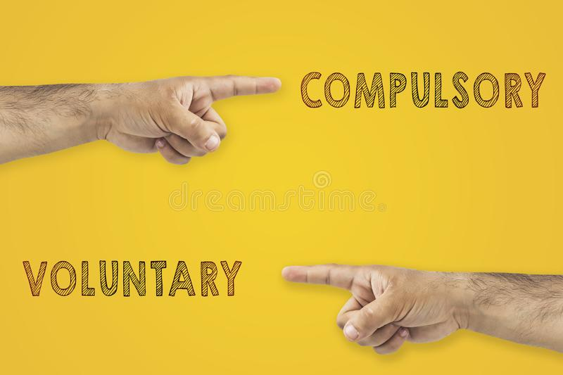 Antonym concept. Hands pointing to different sides. Voluntary or compulsory on yellow background. royalty free stock photography
