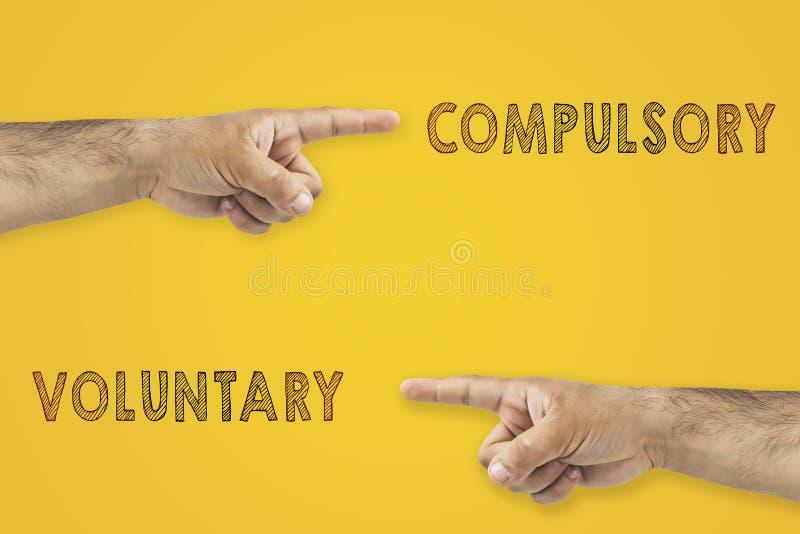 Antonymbegrepp Händer som pekar till olika sidor Frivilligt eller obligatoriskt på gul bakgrund royaltyfri fotografi