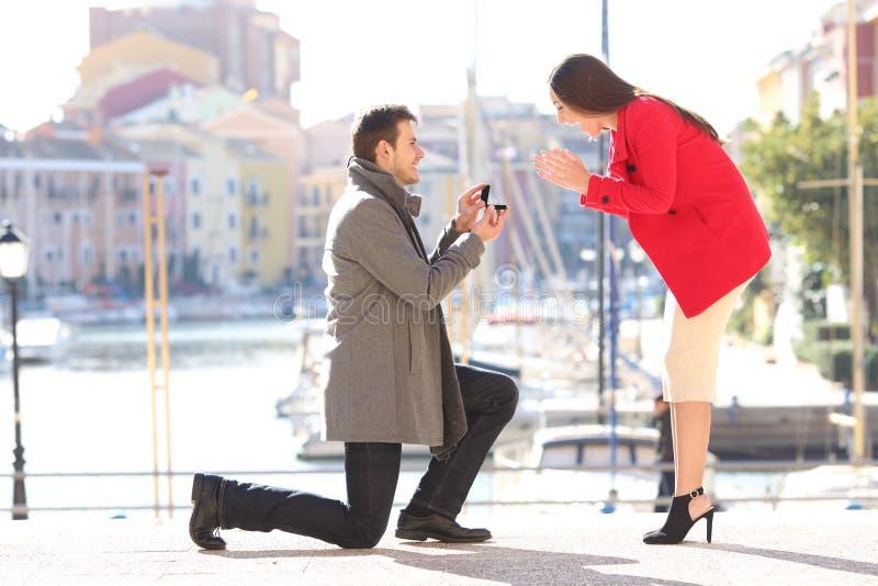 Antrag des Mannbittens heiraten zu seiner Freundin lizenzfreie stockfotografie