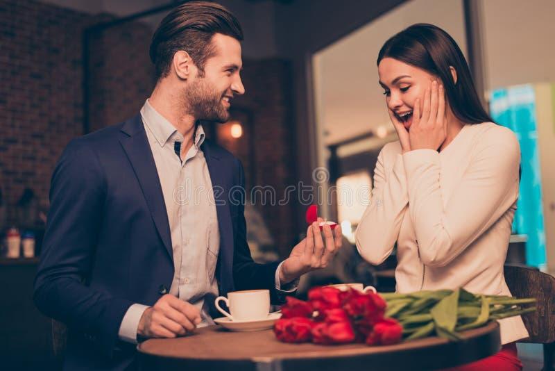 Antrag in einem Café mit unerwartetem Schmuck des Ringes und der Momentflitterwochen machend der Blumen, schellen Sie Konzept-Fra stockfotos