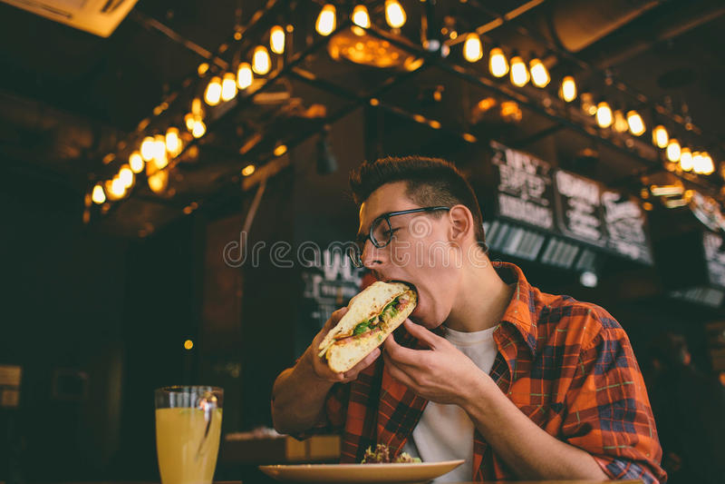 Antropófago em um restaurante e em apreciar o alimento delicioso imagens de stock royalty free