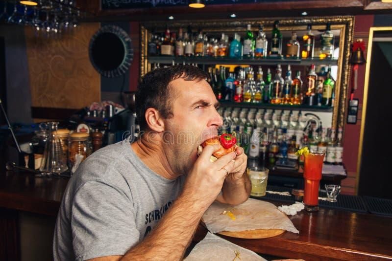 Antropófago joven una hamburguesa foto de archivo