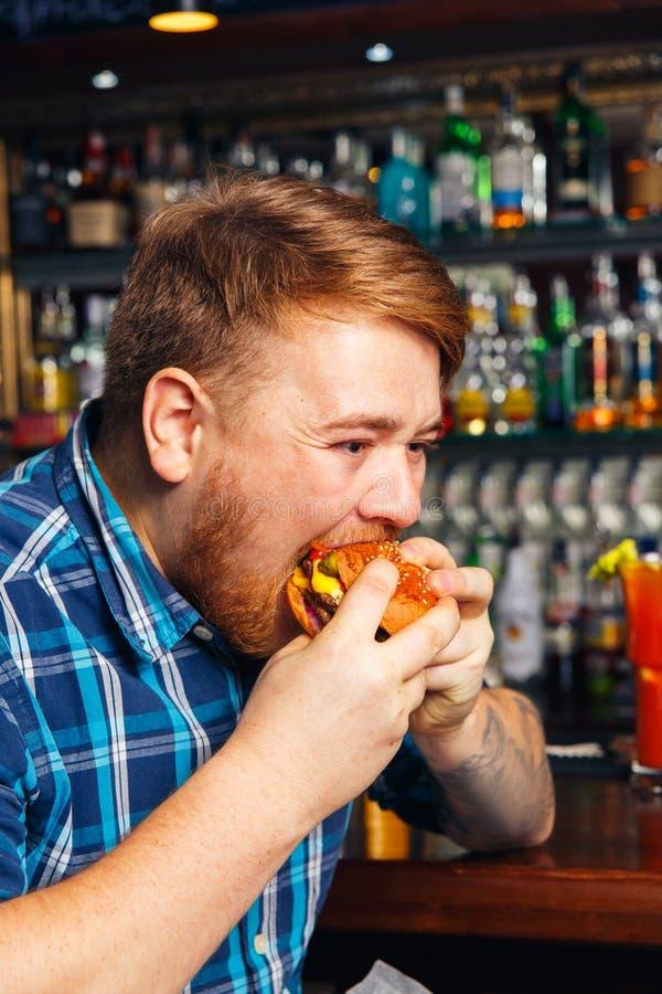 Antropófago joven una hamburguesa fotografía de archivo