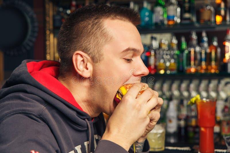 Antropófago joven una hamburguesa fotografía de archivo libre de regalías
