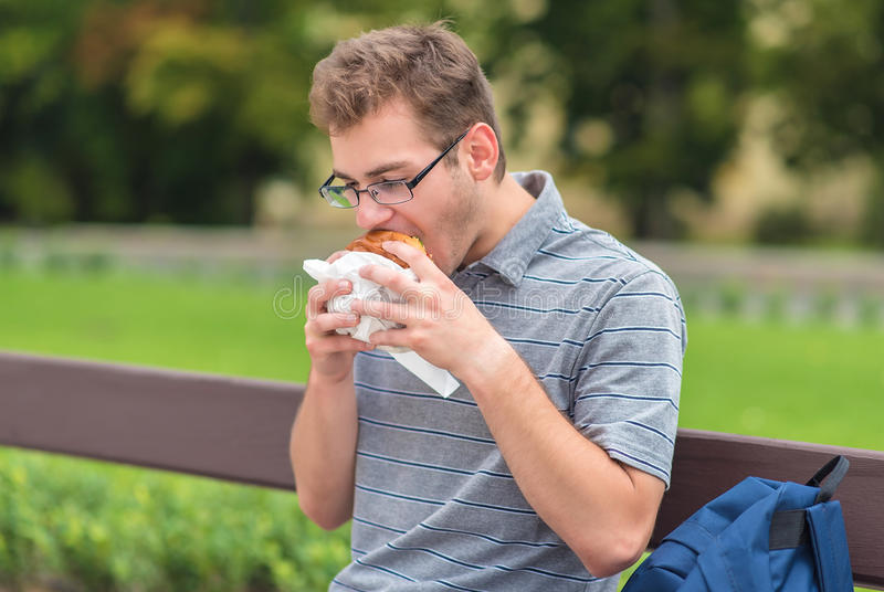 Antropófago joven una hamburguesa fotos de archivo