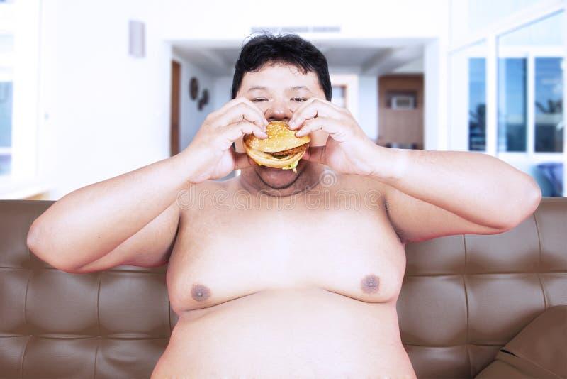 Antropófago obeso voraz una hamburguesa en casa imagenes de archivo