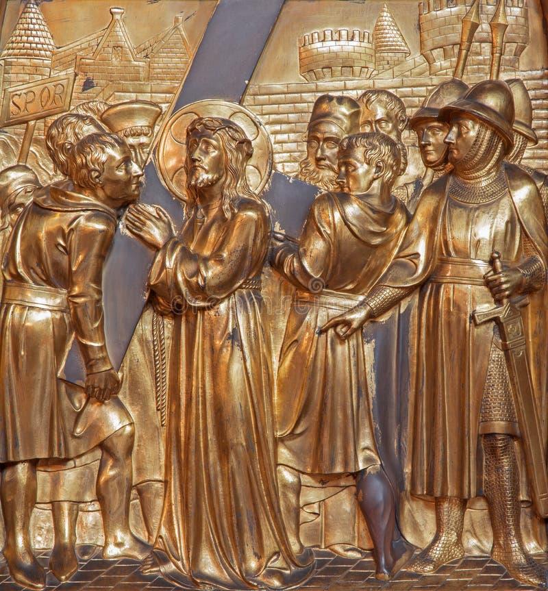 Antwerpen - Simon von Cyrene hilft Jesus, sein Kreuz zu tragen. Asphaltieren Sie Entlastung als Teil des Querweisenzyklus von Jori lizenzfreies stockfoto
