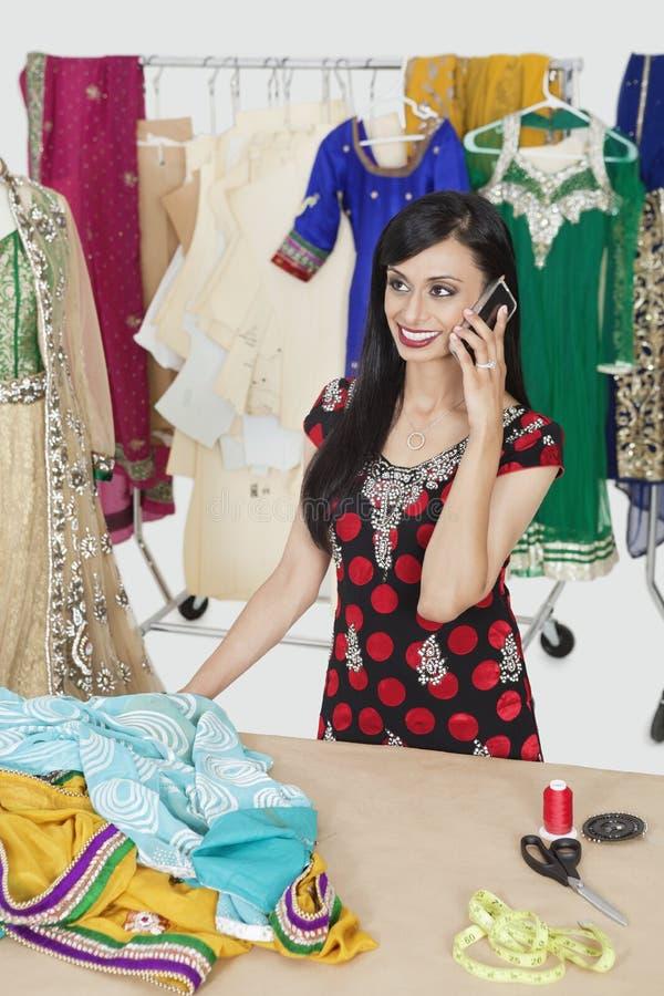 Antwortender Telefonanruf der recht indischen weiblichen Damenschneiderin bei bei Tisch stehen lizenzfreie stockbilder