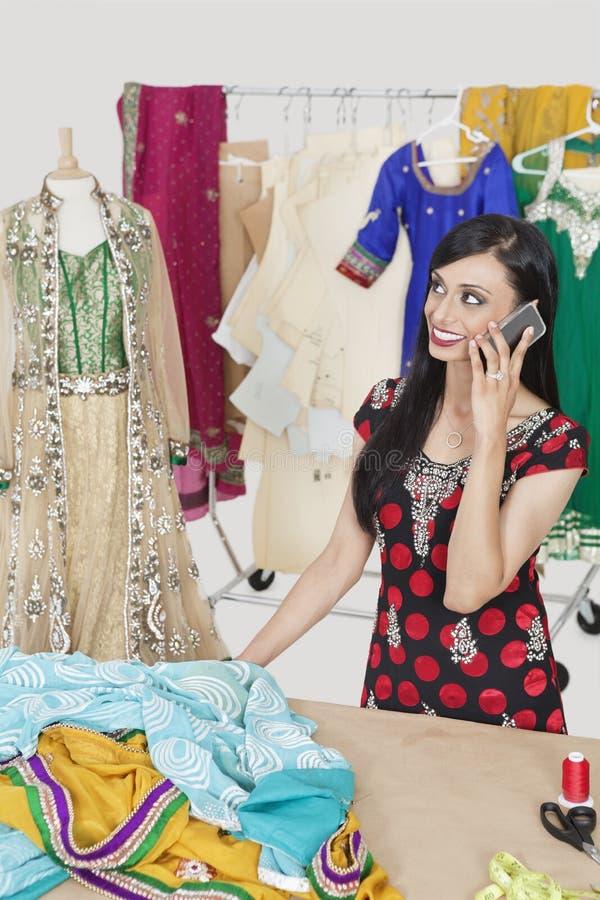 Antwortender Telefonanruf der schönen indischen weiblichen Damenschneiderin bei bei Tisch stehen lizenzfreies stockfoto