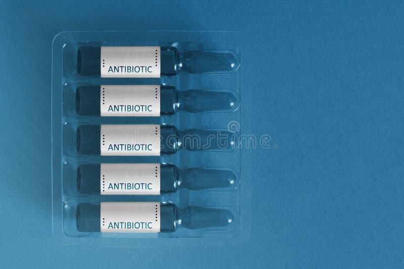Antybiotyki u?ywa? poj?cie Pi?? ampules z narzuta listami wpisowy antybiotyk Pharma biotechnologii sztandar fotografia stock