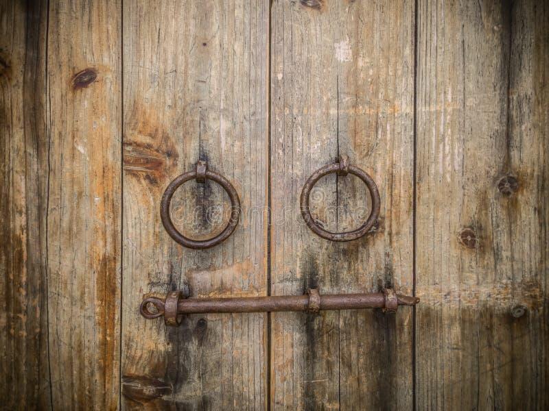 Antyczna drewniana brama z dwa drzwiowego knocker pierścionkami i kędziorkami obrazy stock