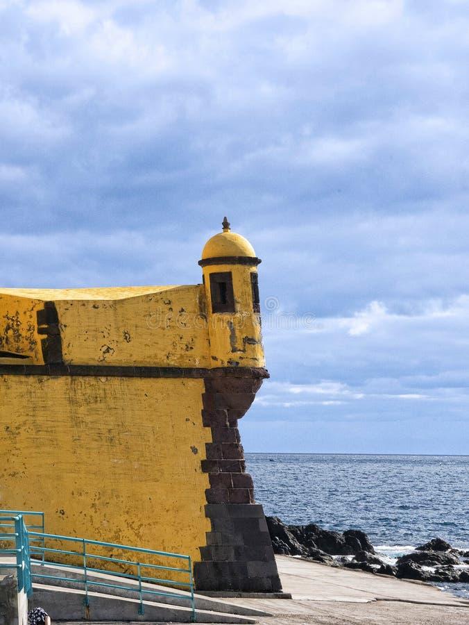 Antyczny żółty forteca Sao Tiago z swój kąpanie platformami w Atlantyckiego ocean obrazy stock