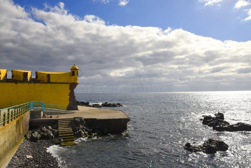 Antyczny żółty forteca Sao Tiago z swój kąpanie platformami w Atlantyckiego ocean zdjęcie royalty free