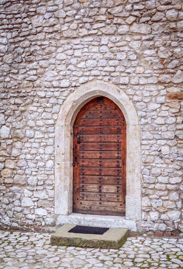 Antyczny drewniany drzwi przy kamienną ścianą obrazy stock