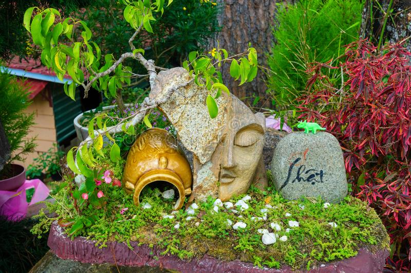 Antyczny dzbanek i rzeźba twarz blisko kwiatów w parku zdjęcie stock