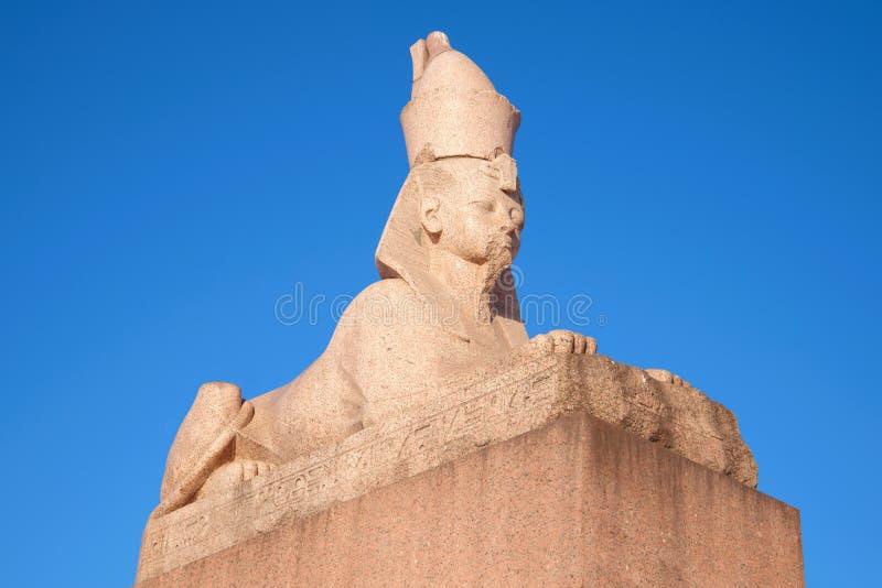Antyczny Egipski sfinks z Uniwersyteckim bulwaru zakończeniem przeciw niebieskiemu niebu katedralny Isaac cupola Petersburg Rosji obrazy royalty free