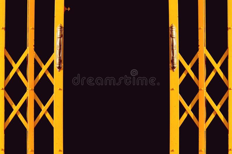 Antyczny kolor żółty rozszerzał metalu drzwi na czarnym tle zdjęcia stock
