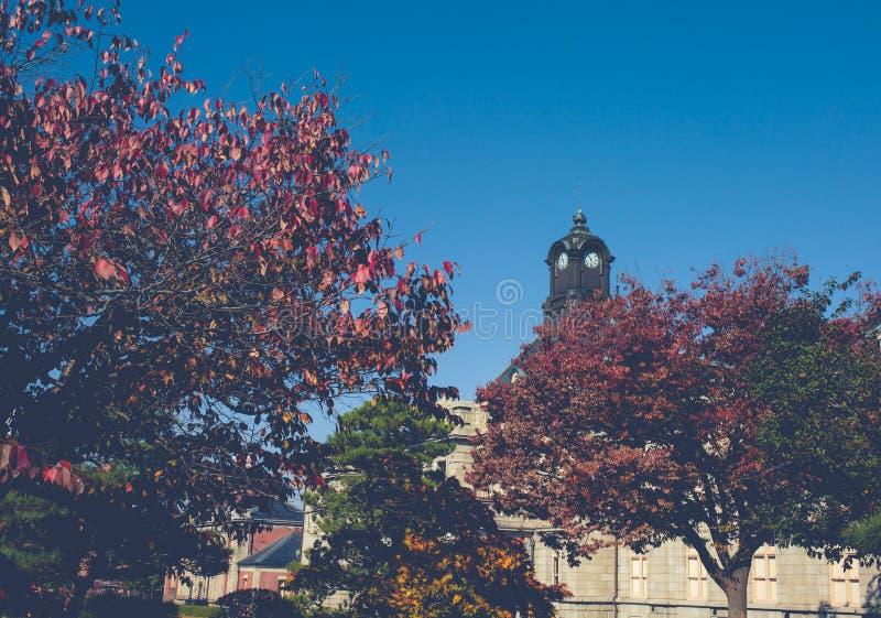 Antyczny zegarowy wierza na dachu stary budynek czerwonych liście, pomarańcze i niebieskich nieb, Jesień w Yamagata, Japonia, roc zdjęcie stock