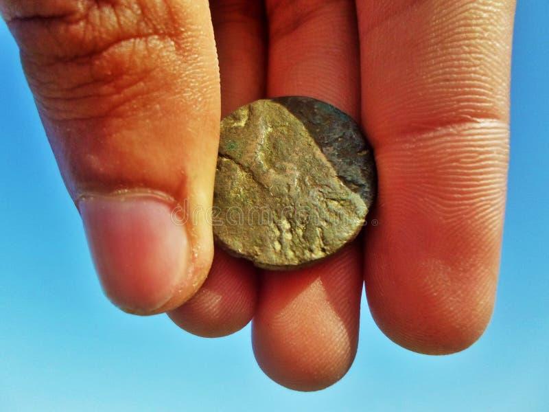 Antyka kamienia moneta w ręce na błękicie obraz royalty free