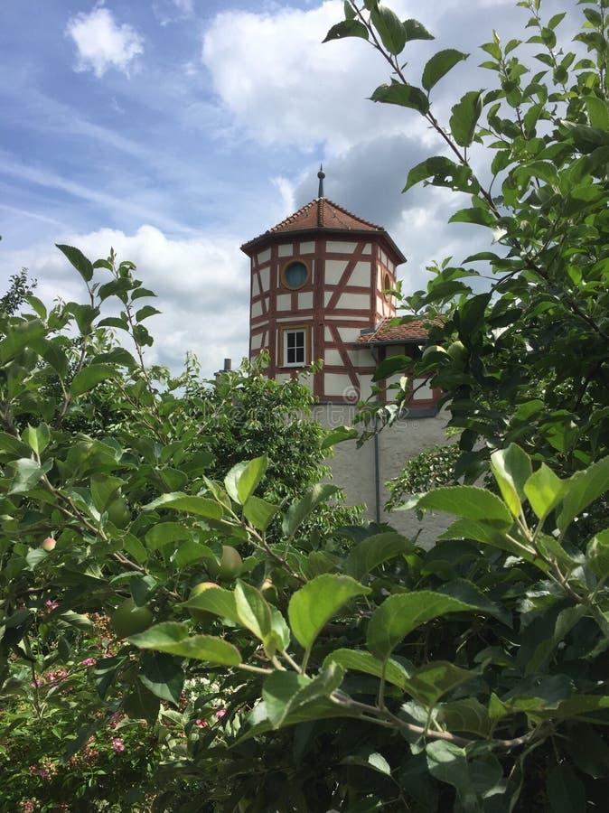 Antykwarska średniowieczna połówka cembrował wierza za czereśniowymi drzewami zdjęcie stock