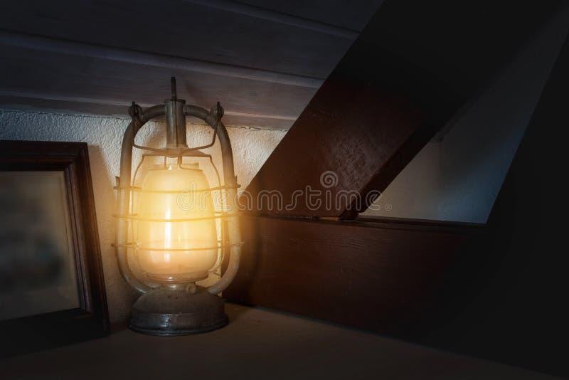 Antykwarska nafciana lampa na drewnianym odkłada palenie z starym obrazem w rocznika stylu fotografia stock