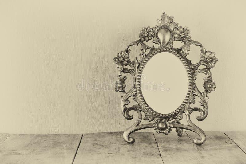 Antykwarska pusta wiktoriański stylu rama na drewnianym stole Czarny i biały stylowa fotografia szablon, przygotowywający stawiać obraz royalty free