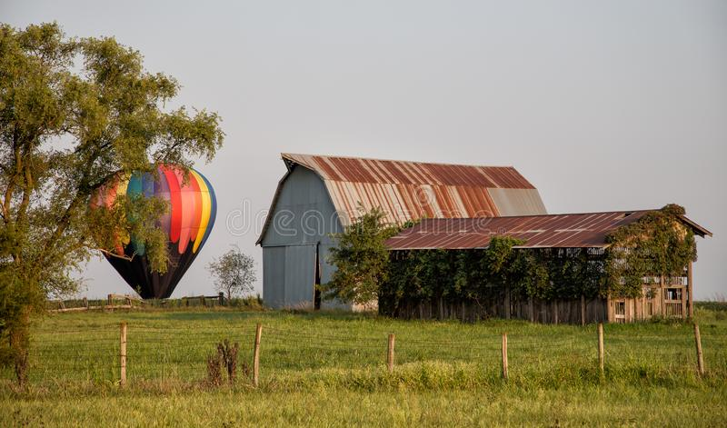 Antykwarska stajnia w polu z kolorowym gorące powietrze balonem zdjęcie royalty free