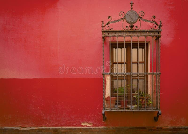 Antykwarski średniowieczny okno z ośniedziałymi stalowymi pręt i Czerwoną bonkrety ścianą obrazy royalty free