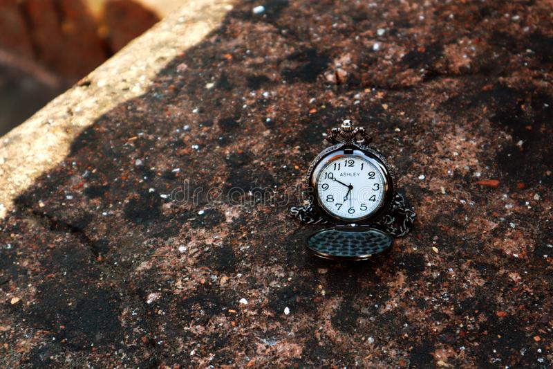 Antykwarski kieszeniowy zegarek na kamień textured półce zdjęcie stock