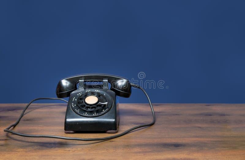 Antykwarski stary obrotowej tarczy telefon na drewnianym biurku zdjęcia royalty free