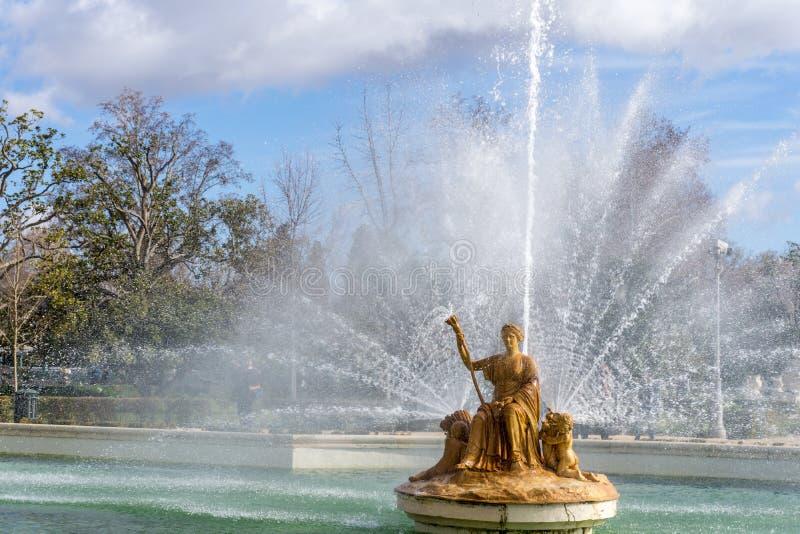 Antykwarski złoty kobiety obsiadanie na tronie w fontannie zdjęcia royalty free