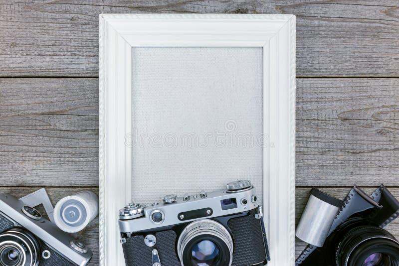Antykwarskie kamery, negatywni filmy i biel fotografii pusta rama na w, zdjęcie stock