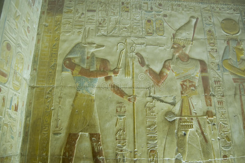 Anubis and Seti wall carving. Ancient Egyptian bas relief sculpture showing the jackal headed god Anubis being worshipped by Pharaoh Seti I. Ancient carving at stock photo